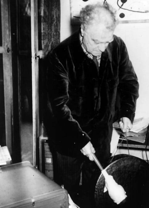 Edgard Varèse playing a gong at home, New York City.